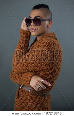 Transgender woman wearing sunglasses standing against gray background