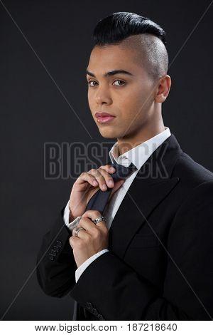 Portrait of transgender adjusting tie while standing against black background