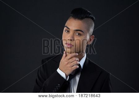 Portrait of transgender woman in full suite over black background