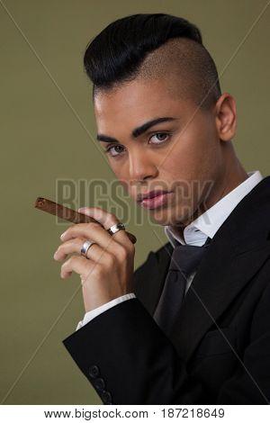 Portrait of transgender woman holding cigarette on green background