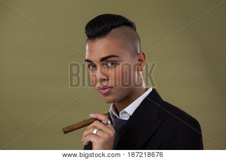 Portrait of transgender woman holding cigarette against green background