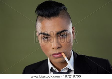Portrait of transgender woman with cigarette in mouth over green background