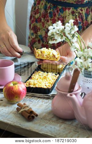 Woman in floral dress cut of apple pie. Autumn breakfast: fruit tart tea cinnamon on rustic wooden background. Sweet piece of cake in the hands of a young housewife