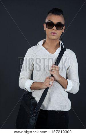Portrait of transgender woman with bag against black background