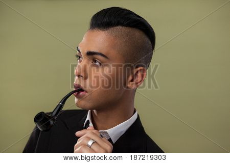 Close up of transgender woman with smoke pipe on green background