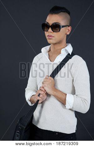 Transgender woman holding bag against black background