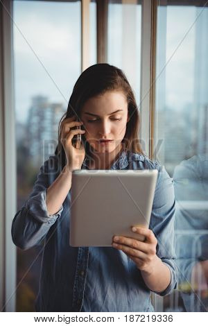 Woman talking on mobile while looking at tablet in home
