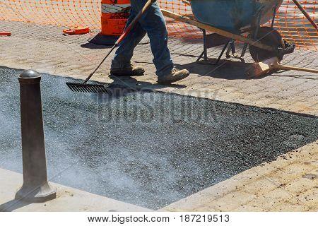 Men hard working on asphalting road with shovels men road is under construction