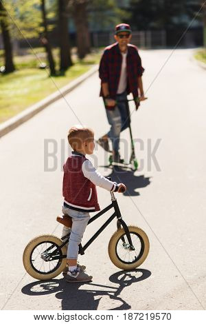 Dad with son on scooters in park during day