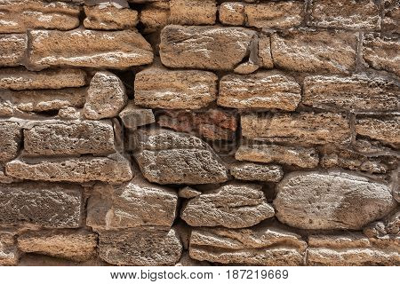 The masonry of an ancient stone wall eroded. Close-up