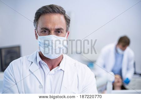 Portrait of confident dentist in surgical mask at dental clinic