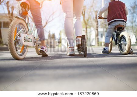 Photo from bottom of family on scooters in park during day