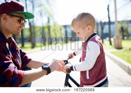 Dad with small son on bike ride in park