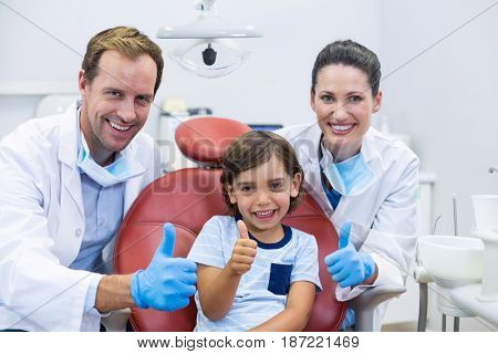 Portrait of smiling dentists and young patient showing thumbs up in dental clinic