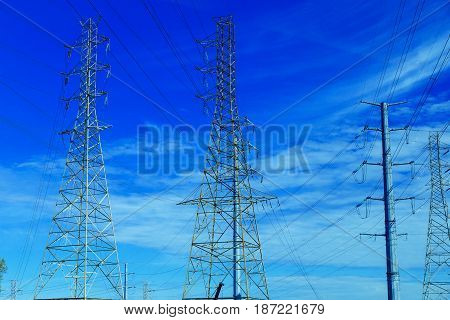 electricity post against blue sky with cloud, chaotic wire with nest on pole electric pole with wires against the sky clouds