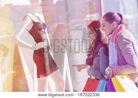 Young female friends window shopping