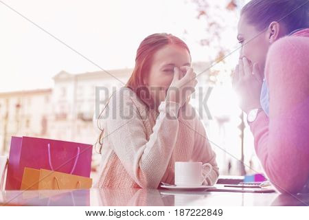 Happy women gossiping at outdoor cafe