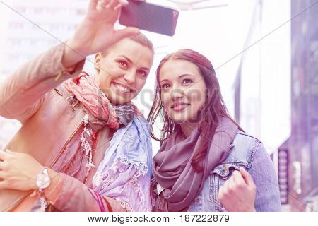 Women in jackets taking self portrait through mobile phone