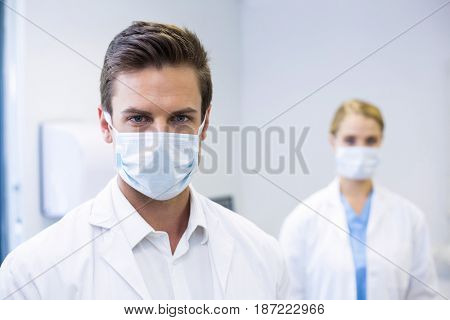 Portrait of dentist wearing surgical mask while his colleague standing in background