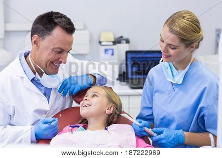 Dentist and nurse interacting with a young patient in clinic