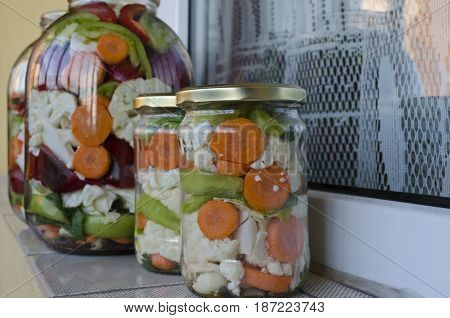 Pickled organic vegetables in glass jars with marinate