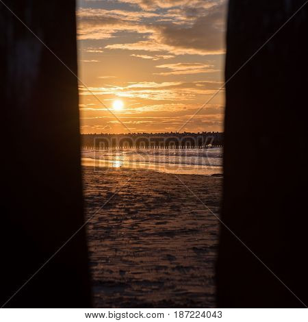 Sunset through piles at the North Sea beach of Cadzand Holland
