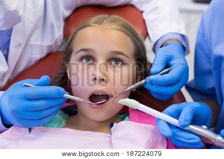 Mid section of dentist and nurse examining a young patient with tools in clinic