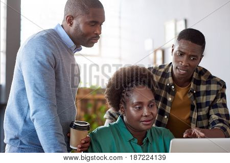 Three casually dressed young African business colleagues looking focused while working on a laptop together at a table in a modern office