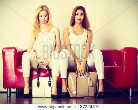 Fashion clothes clothing accessories trendy outfits concept. Two women wearing light outfit and black high heels sitting on red sofa presenting bags