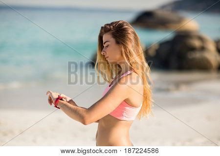 Side view of young woman looking at wristwatch while standing on shore