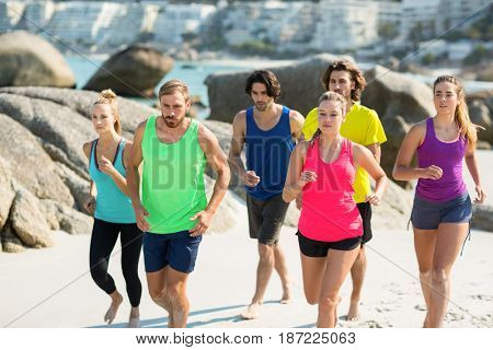 Friends jogging on shore at beach