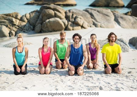 Friends meditating while kneeling on shore at beach