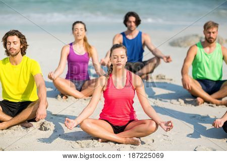 Friends meditating in lotus position on shore at beach