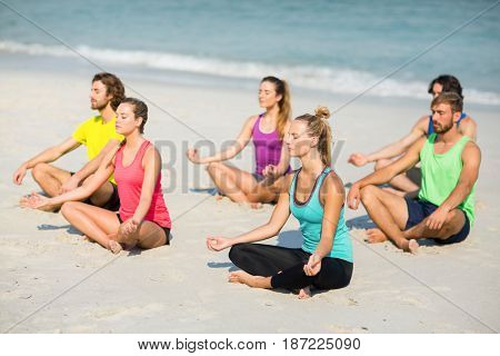 Friends meditating on shore at beach