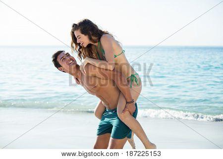 Happy boyfriend piggybacking girlfriend on shore at beach