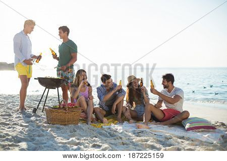 Happy friends having drinks by barbecue at beach against sky