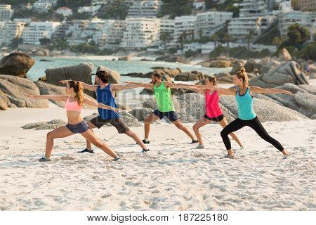 Full length of friends practicing warrior position on shore at beach