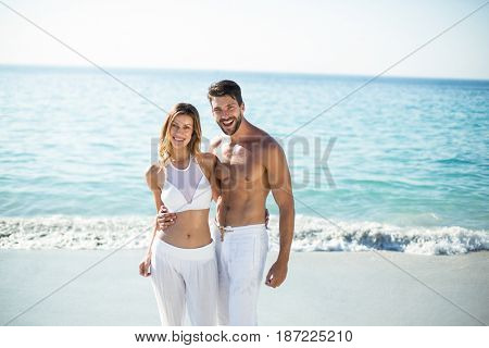 Portrait of young couple standing with arm around on shore at beach