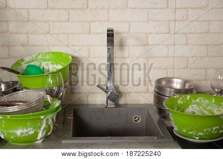 Kitchen utensils with dirty dishes need a wash