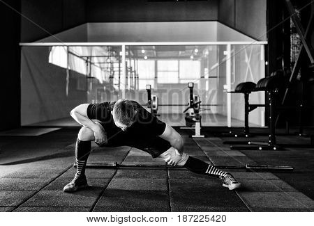 Young man preparing muscles before training. Muscular athlete exercising in gym. Fit man stretching. Professional sportsman warming-up. Full body length portrait