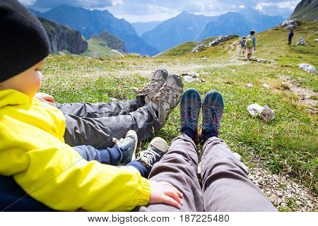 Family in hiking boots on the background of mountains. Family on trekking day in the mountains. Mangart Julian Alps National Park Slovenia Europe. Travel Lifestyle Concept.