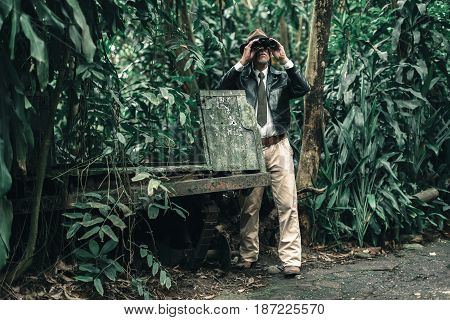 Explorer Looking With Binoculars Standing In Bush Next To Car Wreckage.