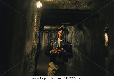 Senior Explorer With Hat In Dark Cave Inspecting Environment.