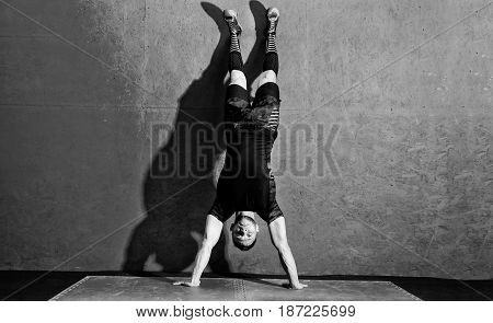 Athlete doing push ups on his hands while standing upside down near red wall. Full body length portrait