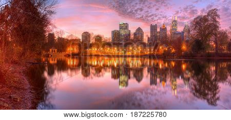 Beautiful panoramic view of Lake Clara Meer illuminated Piedmont Park Aquatic Center and Midtown Atlanta in autumn dusk USA poster