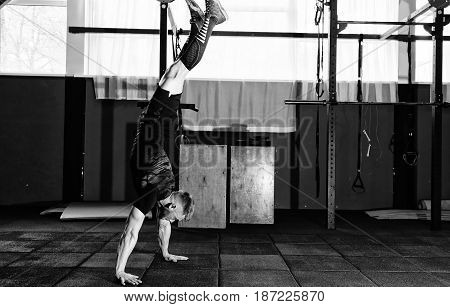 Athlete walking on his hands standing upside down in gym. Workout lifestyle concept. Full body length portrait