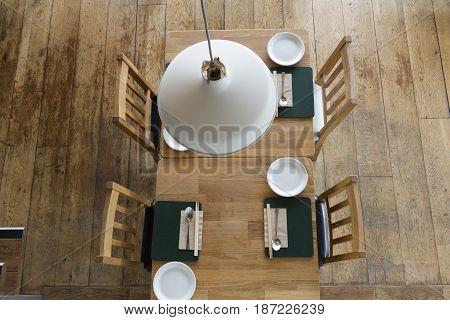 Overhead Of Restaurant Furniture Under Hanging Lamp