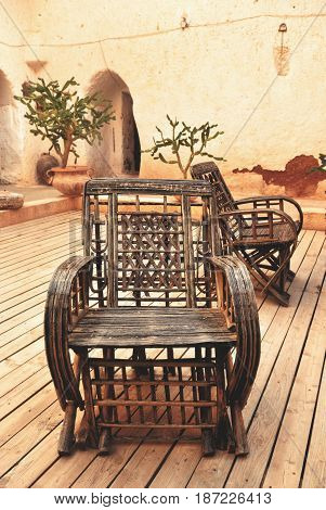Wicker armchair with old wall background on patio in mexican style