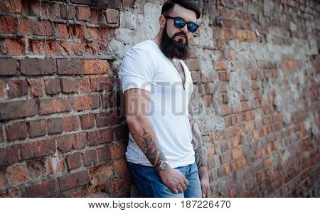 Brutal Bearded Man With Tattoo In Jeans And White Tee-shirt Standing Near A Brick Wall. Bricks Wall