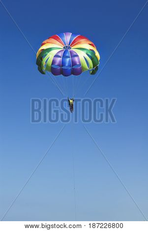 Skydiver on colorful parachute in sunny blue sky. Active lifestyle. Extreme sport.